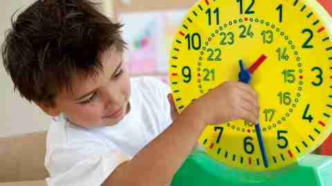 A boy playing with a toy clock at the beginning of the new school year
