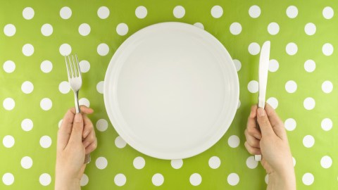 A woman with ADHD holds a knife and fork next to an empty plate, a metaphor for her weight loss plan