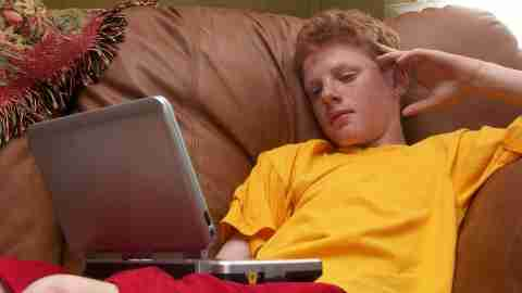A teen with ADHD uses a laptop on the couch