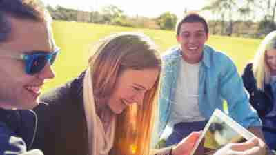 A group of teens laughing together in a park. Their parents wonder how to motivate a teenager.