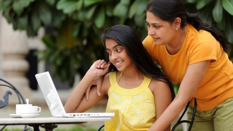Mother and daughter working on laptop in outdoors. Spending quality time together is one way to motivate a teen.