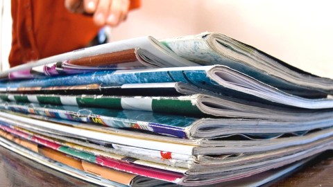 A person sorts through a pile of magazines and mail to reduce clutter and chaos.