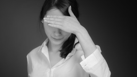 A women with ADHD is ashamed and hides her face.