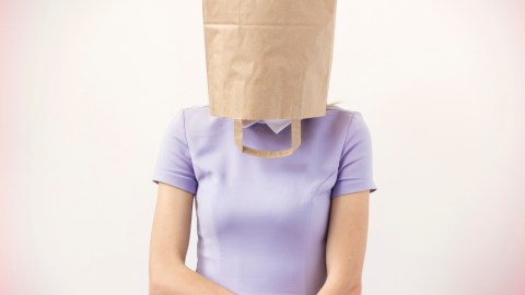 A woman with ADHD is ashamed and puts a bag over her head.