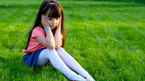 A little girl with ADHD sits in the grass looking sad.