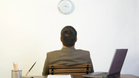 A man faces away from his desk and stares at the clock, wondering how he can stop negative thoughts