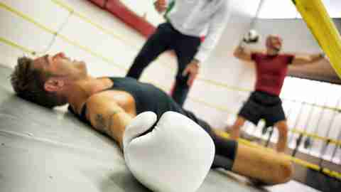 A boxer lying on the floor of the ring after losing a fight. He is weighed down by negative thoughts.