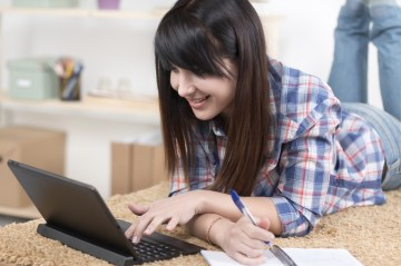 A teen with ADHD uses assistive technology to complete her homework.
