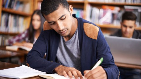 A student writes in a notebook in the library. He could benefit from assistive technology.