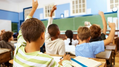 Hands all raised in classroom as teacher discusses medication monitoring