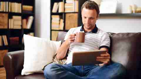 Man drinking coffee and reading positive affirmations on his laptop