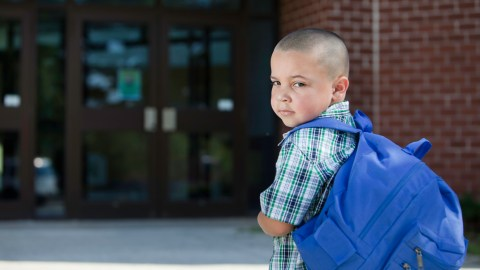 A boy with a language processing disorder stands outside his school