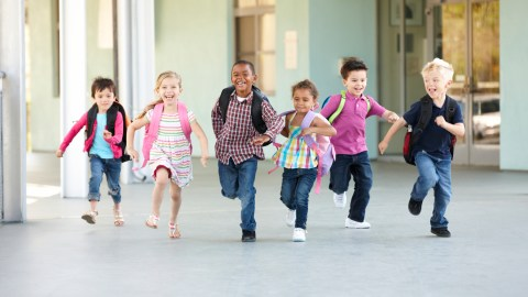 A group of elementary school children with ADHD run outsite to expend excess energy.