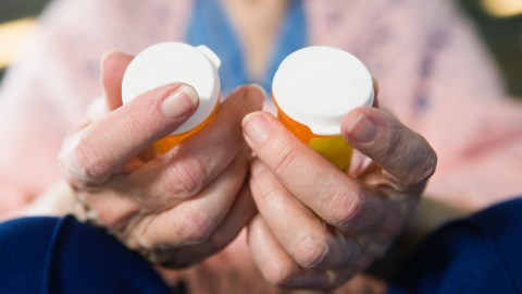 """A woman holds two prescription bottles in her hands and wonders, """"How does ADHD medication work?"""""""