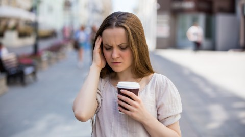 "A woman walks down the street holding a coffee and wonders, ""How does ADHD medication work?"""