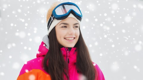 """A woman with ADHD smiles as snow falls around her ski hill, and wonders, """"How does ADHD medication work?"""""""
