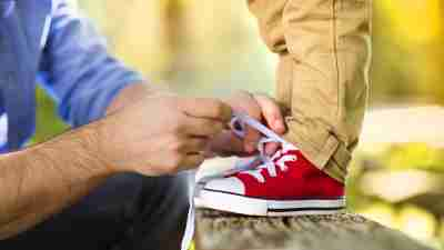 A father ties his son's shoes while thinking about how to be a better dad.