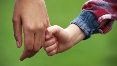A parent and child holding hands as the parent tries to mend their damaged relationship