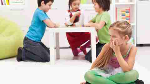 A girl with ADHD sits apart from a group of children playing a game. She could use YouTube videos for kids to help her learn social skills.