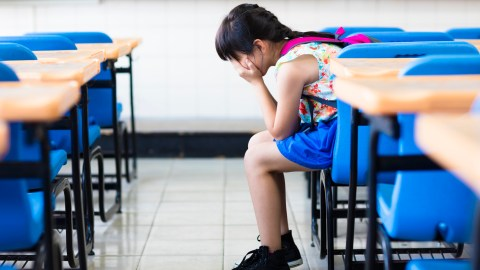 A girl crying in a classroom and wondering how we can improve education
