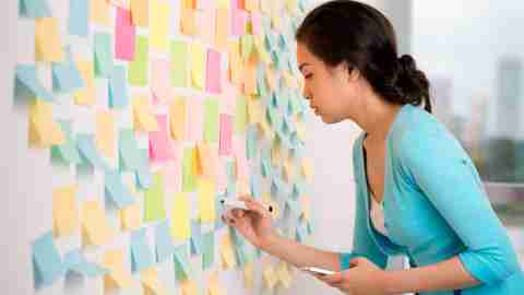 Woman with ADHD covering wall with colorful post-it notes to organize life