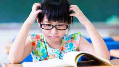 Girl with ADHD looking frustrated and grabbing at hair while trying to read