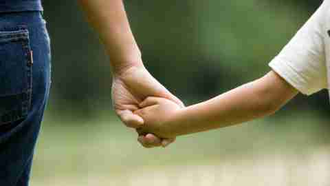 Close up of mother holding hand of ADHD child while walking outside