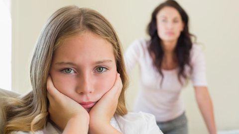 Upset girl with ADHD frowning with mother in background disciplining