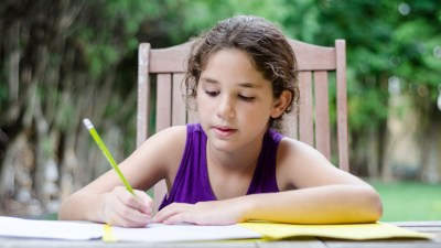 Girl with ADHD doing homework outside at table