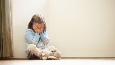 Little girl with ADHD sitting in corner with hands on face