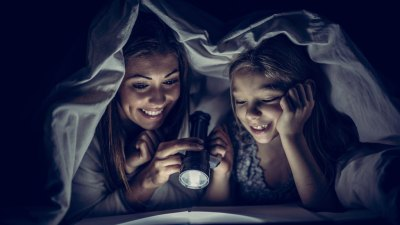 Mother reading book with ADHD daughter (a reluctant reader) under comforter with flashlight at night