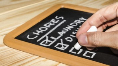 Person with ADHD checking off list of chores from mini blackboard