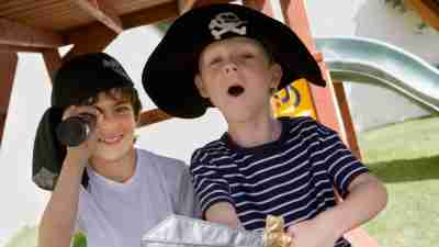 Two boys with ADHD playing pirates at playground in costumes