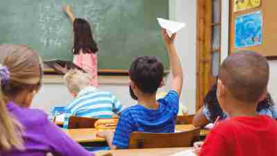 Student with ADHD about to throw a paper airplane at teacher in classroom