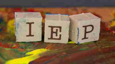 "Three blocks spelling ""IEP"" on paint covered table, which is important to know about if a child has ADHD"