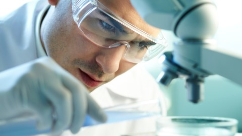 A scientist with ADHD uses hyperfocus to examine a sample under a microscope.