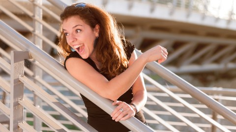 A smiling woman with ADHD leans on a fence.