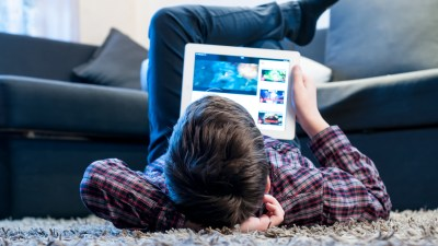 ADHD teenager with tablet while lying on the floor in the room