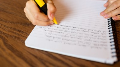 A teen with ADHD writing something down to finish his school work