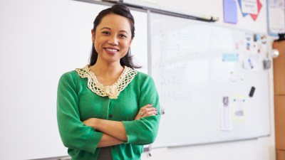 Portrait of confident female teacher who has ADHD students in classroom