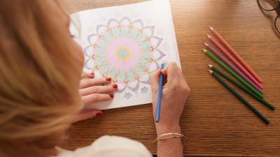 Overhead view of ADHD woman drawing in adult coloring book with color pencils for anti-stress