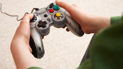 Hands of ADHD child holding video game control pad
