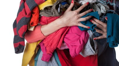 ADHD woman holds pile of dirty clothes