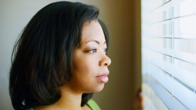 Mom with ADHD feeling overwhelmed looking out the window for help