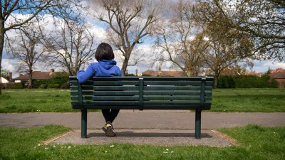 ADHD Woman sitting on bench with back turned looking at the park thinking