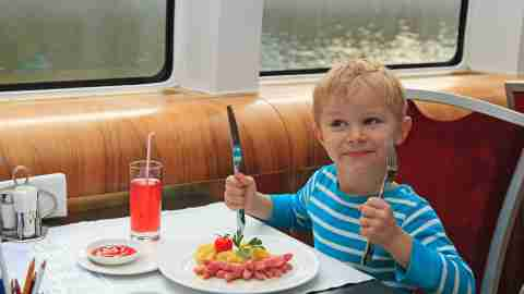A boy eating in a restaurant; his behavior in booths was how his parents knew he had ADHD