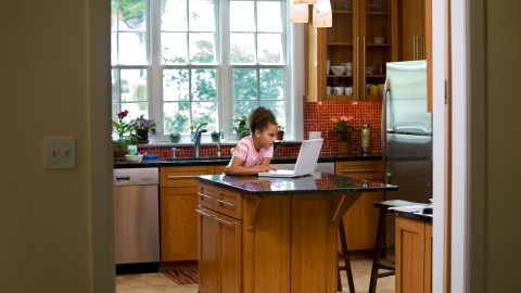 Young girl working on her homework standing in the kitchen because she has problems when sitting down