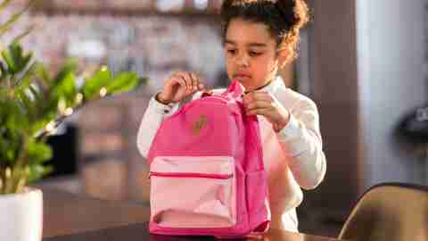A young girl packing her homework into her backpack to avoid problems the next day