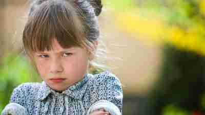 Pretty funny moody young child girl outdoor feeling angry and unsatisfied on blurred summer green background. Children tantrum concept.