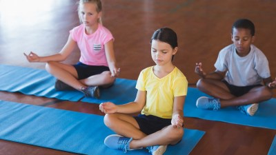 A group of students practice mindfulness exercises in gym class